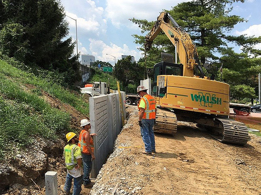 workers installing an AFTEC concrete retaining wall